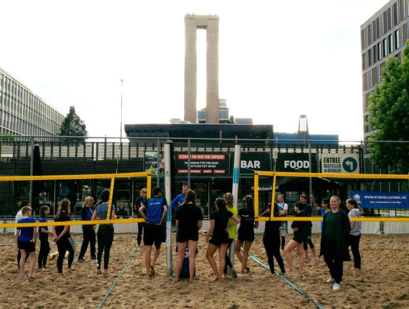Jeugdleden staan in een cirkel tijdens de beachvolleybaltraining op de VU Campus.